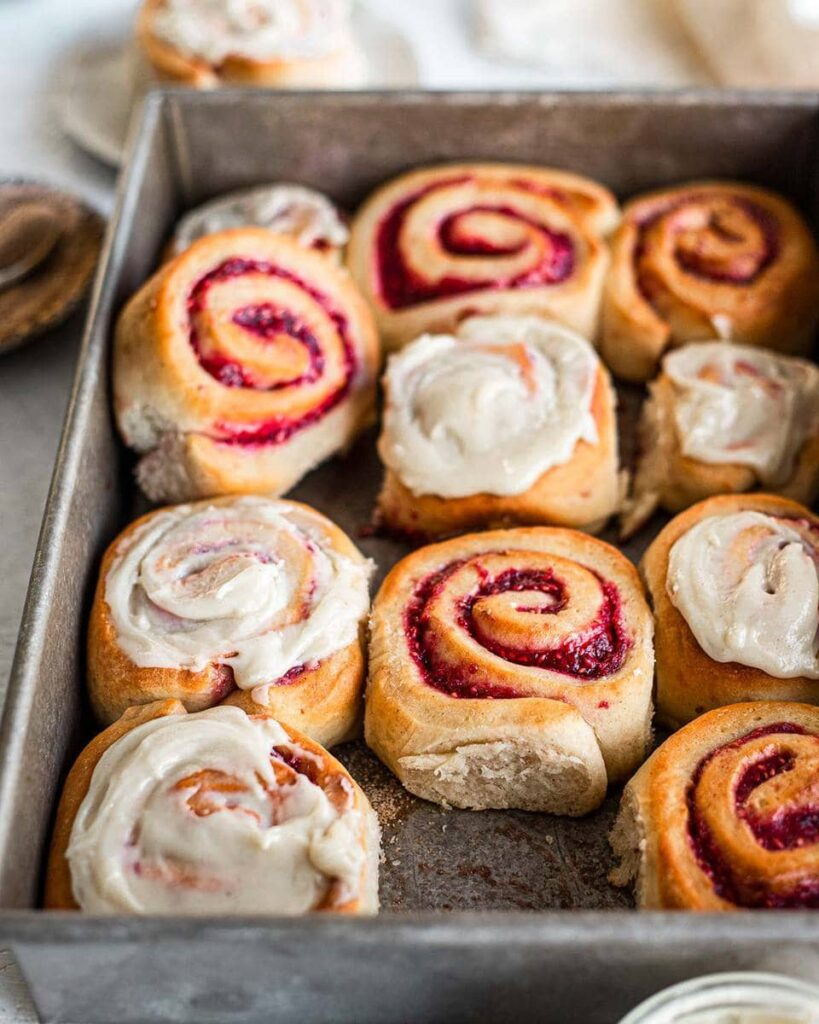 Jam Donut Cinnamon Rolls in baking tray. Some are iced and some are not. One roll is removed showing the feathery and soft edge of one of the brioche rolls. Another example of the versatility of crazy vegan dough