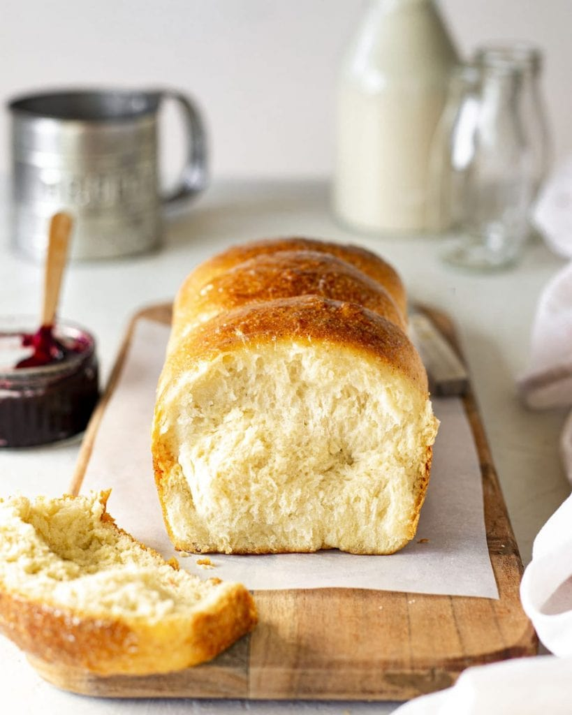 Vegan brioche french bread on chopping board. Slice cut off showing golden and soft interior. The board is surrounded by brioche accompaniments such as jam. Also can be used as vegan crazy dough.