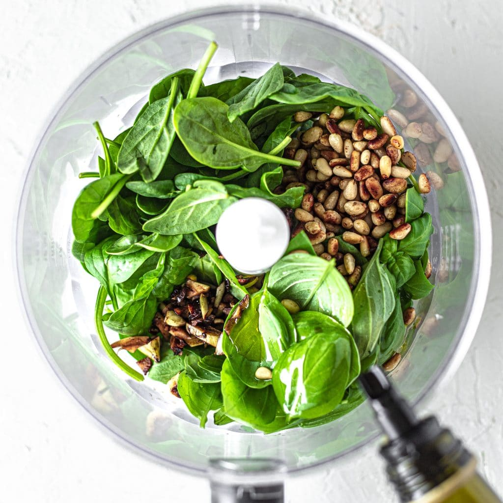 Spinach, basil, pine nuts, garlic and olive oil in food processor for pesto