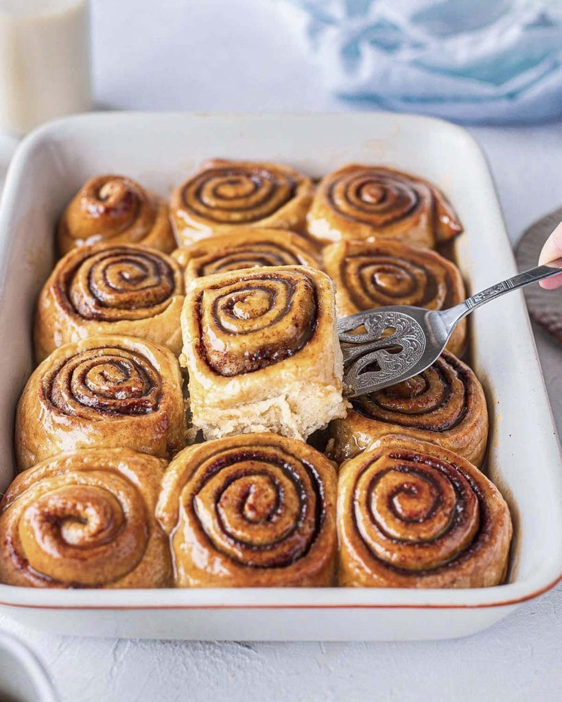 A dozen of vegan sticky cinnamon buns in baking tray with one centre bun lifted out with a cake server exposing feathery and soft edges. First example of the versatility of vegan brioche dough.