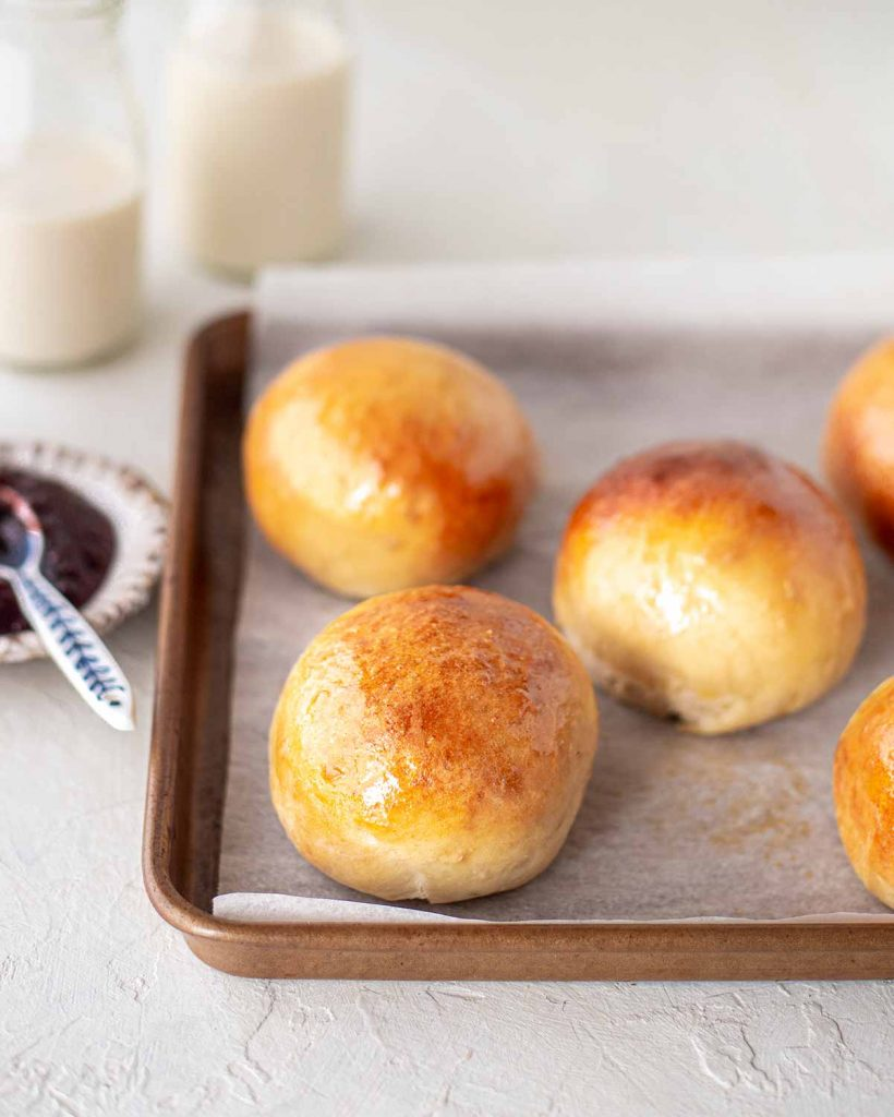 Vegan brioche buns on lined baking tray