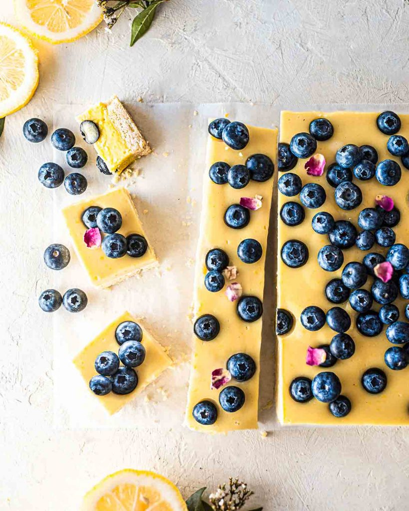 Flatlay of creamy vegan blueberry lemon bars