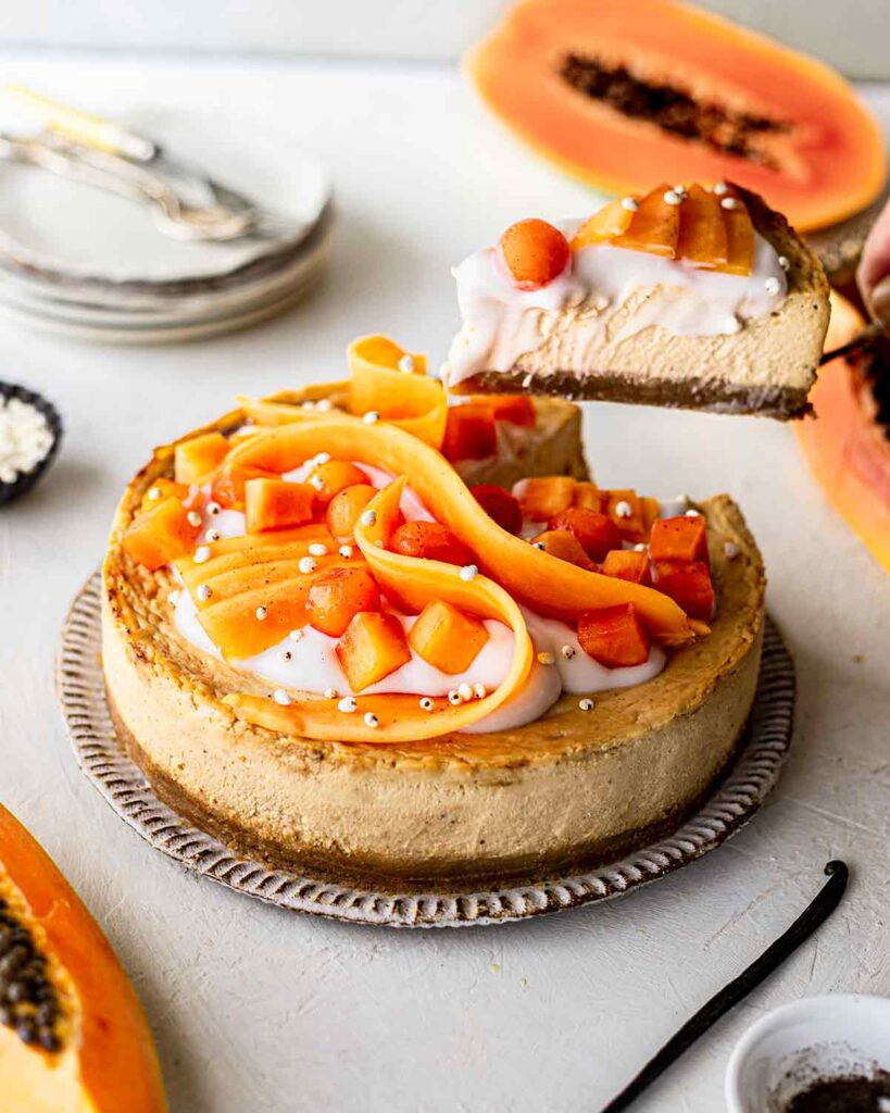 Papaya vanilla cheesecake on plate with slice lifted out showing its creamy texture