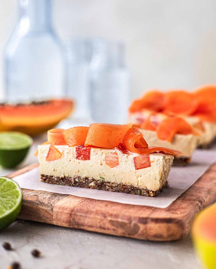 A row of papapya lime slice on a chopping board. Each slice has bits of papaya in the slice and shaved papaya on top