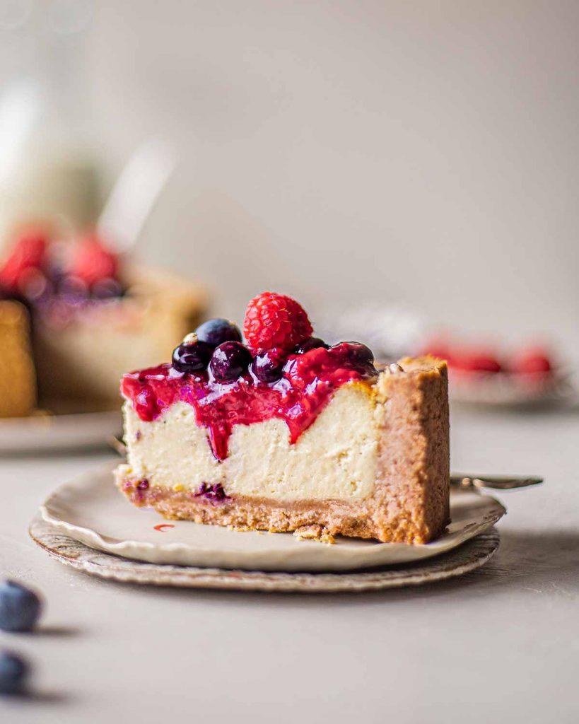 Close up of baked cheesecake slice with berry compote dripping down smooth filling