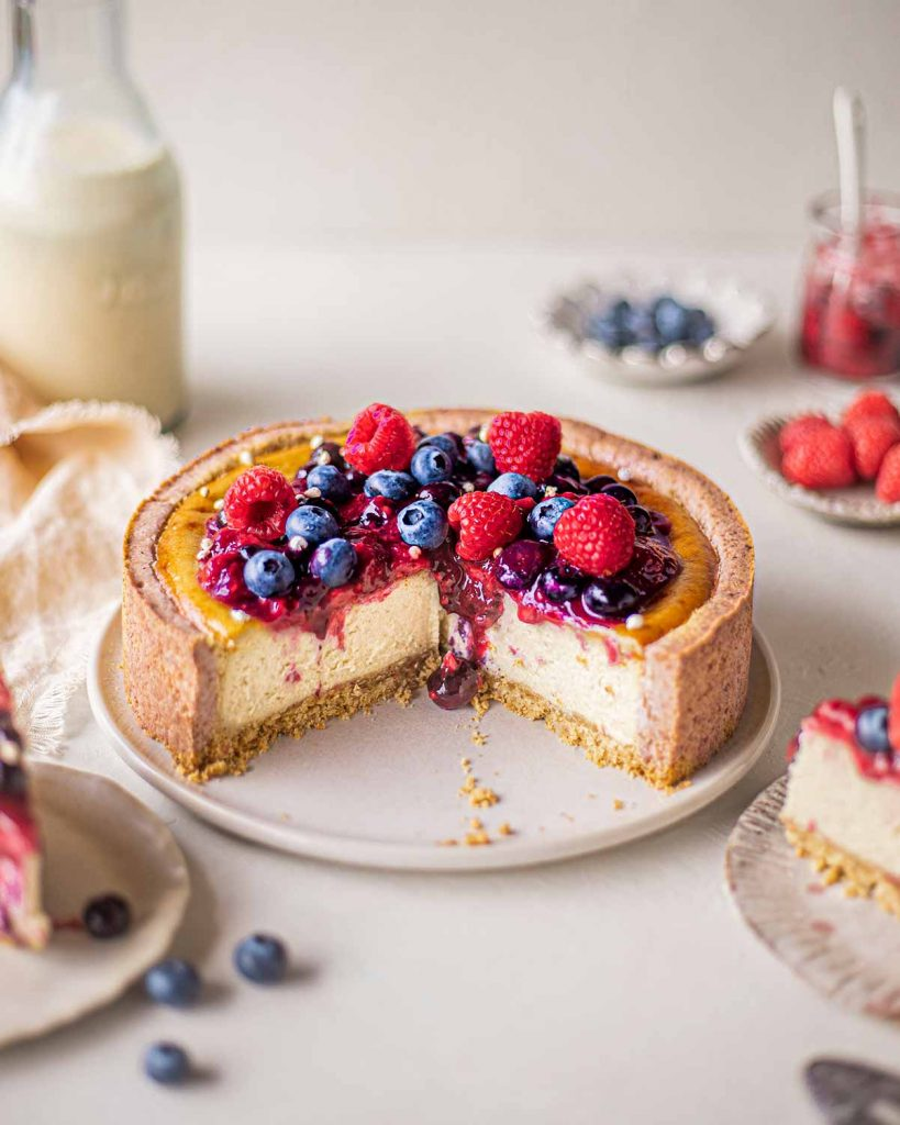 Cross section of baked cheesecake (vegan) with drip of berry compote on luscious creamy cheesecake filling