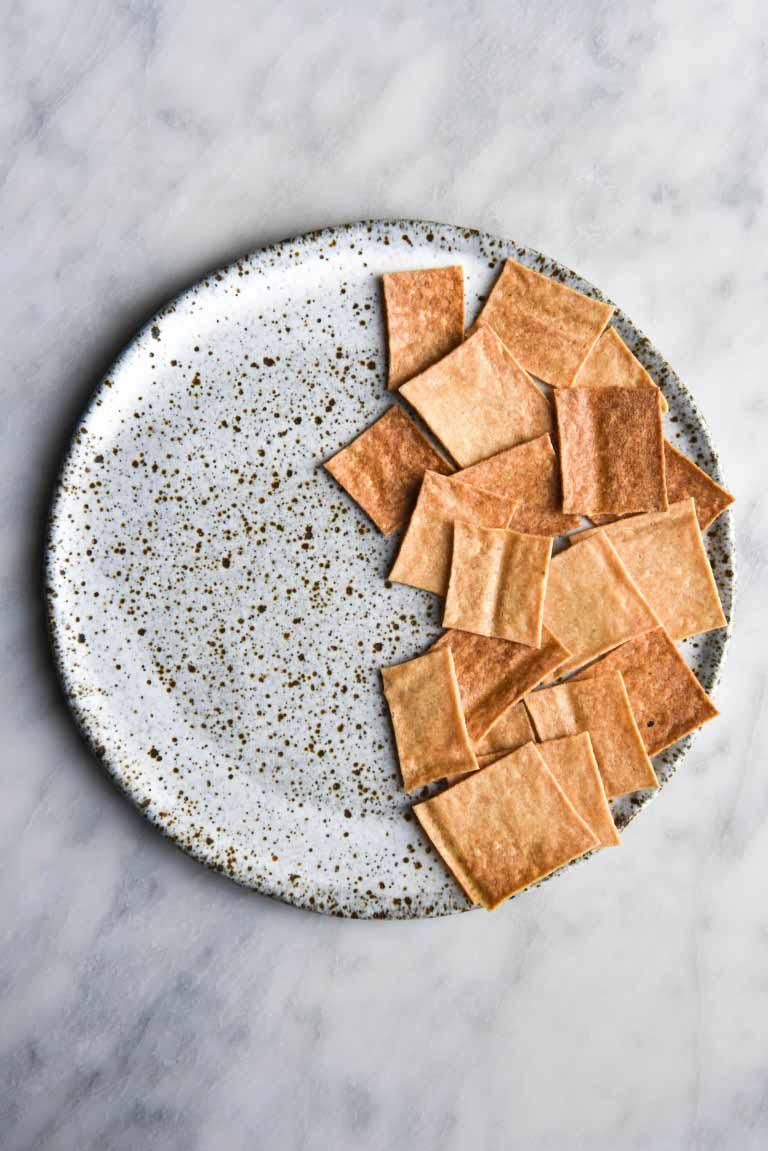 Vegan gluten free sourdough crackers arranged on half of a ceramic hand made plate