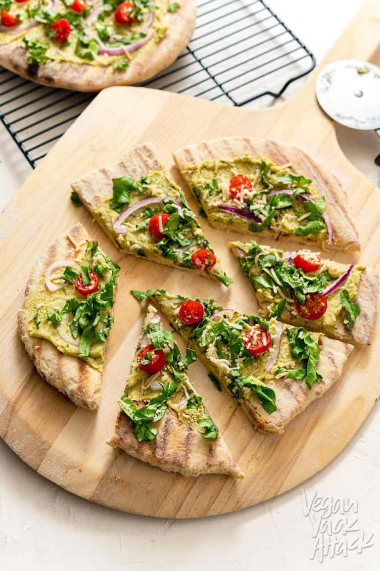Vegan Grilled Sourdough Flatbread with white bean basil spread and chopped tomatoes on chopping board