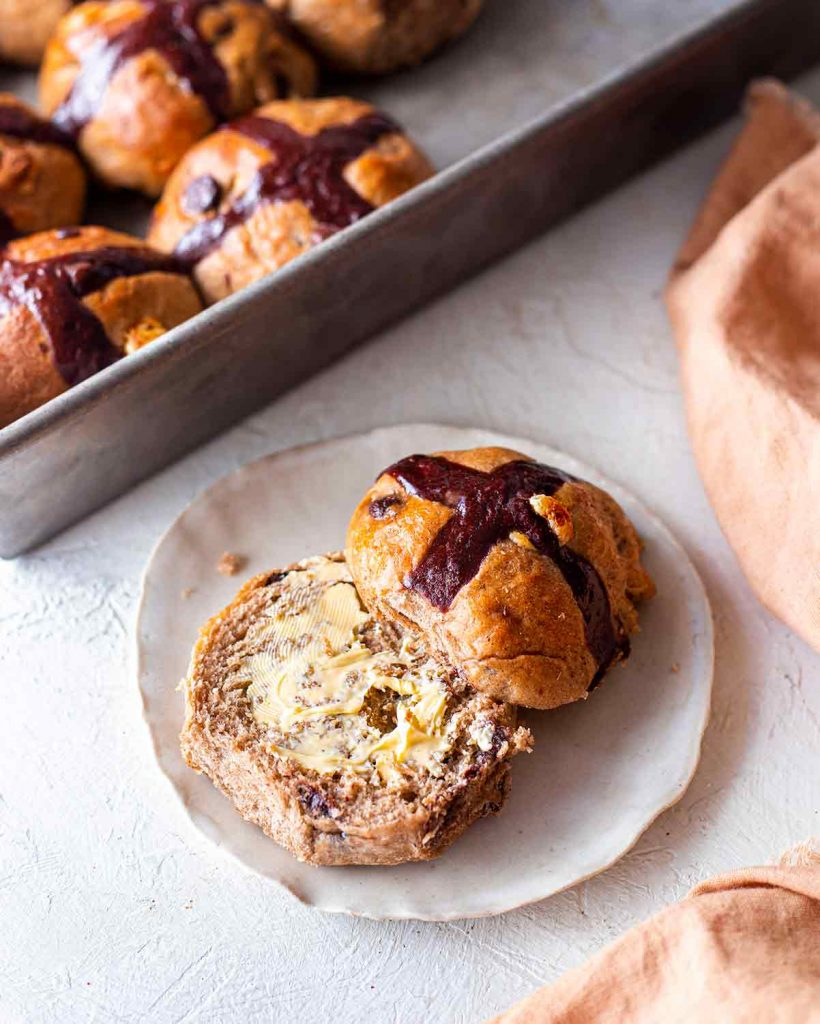 Close up of buttered vegan chocolate chip hot cross bun