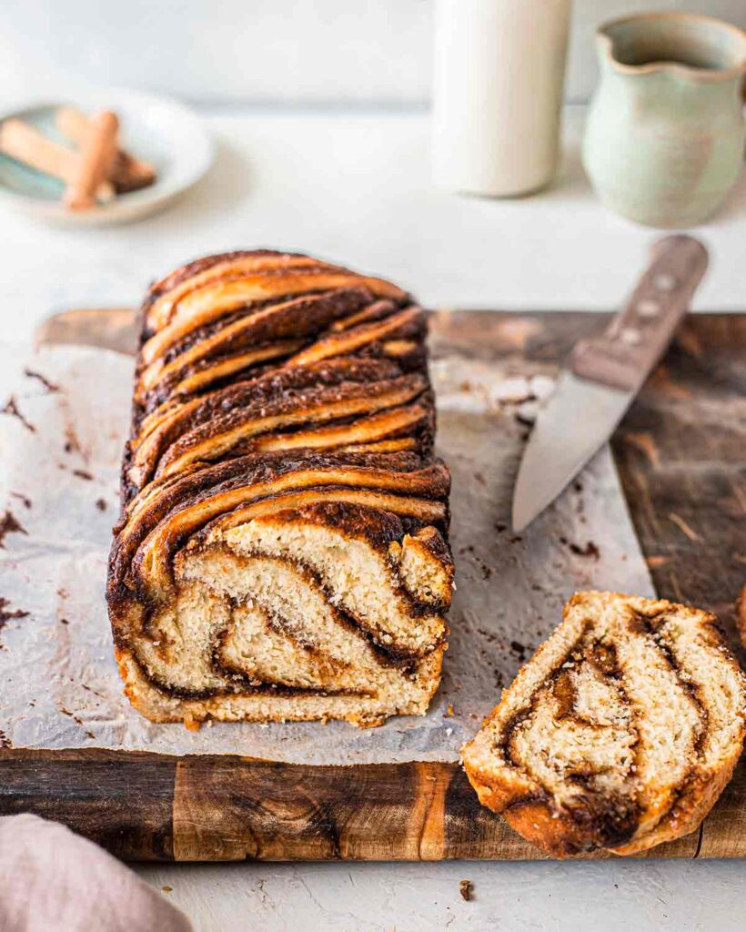 Vegan Cinnamon Babka with slice cut off showing interior. Babka is on a rustic piece of baking paper and a chopping board with a knife.