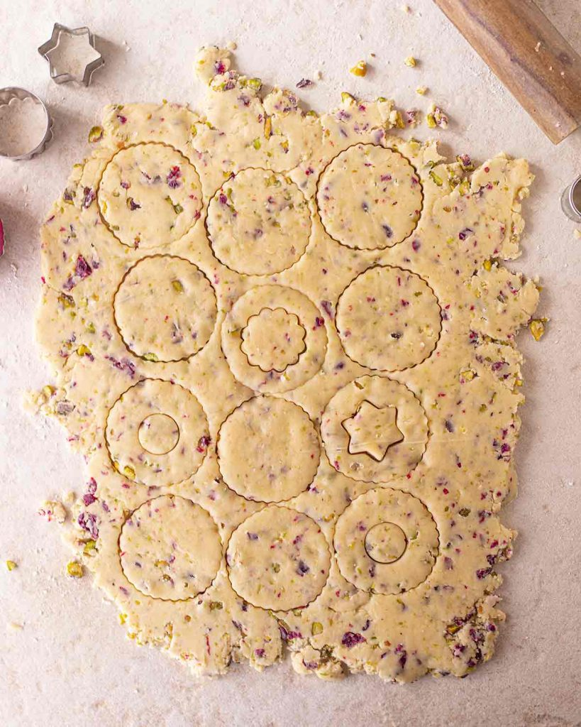 Cookie cutter shapes in slab of vegan christmas shortbread dough