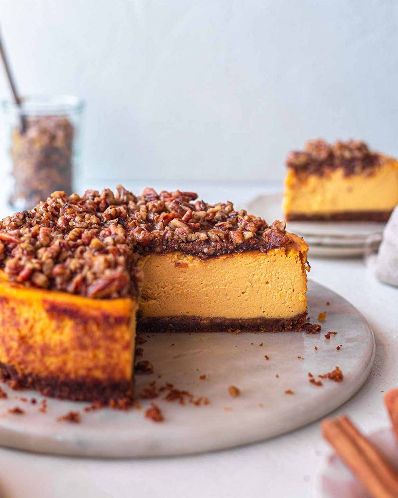 Close up of baked vegan pumpkin cheesecake with a pecan crumble on a serving platter