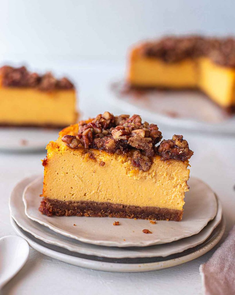 Close up of a slice of vegan pumpkin cheesecake on a stack of plates