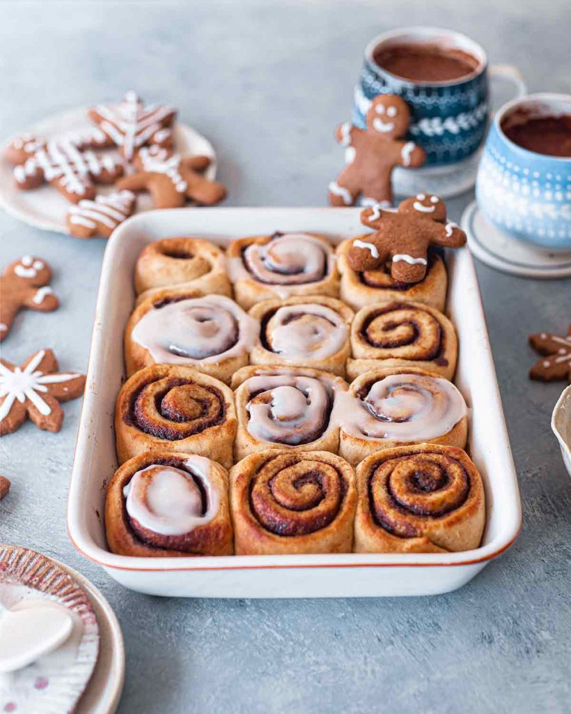 Side angle of vegan gingerbread scrolls in baking tray surrounded by vegan gingerbread cookies and hot chocolate