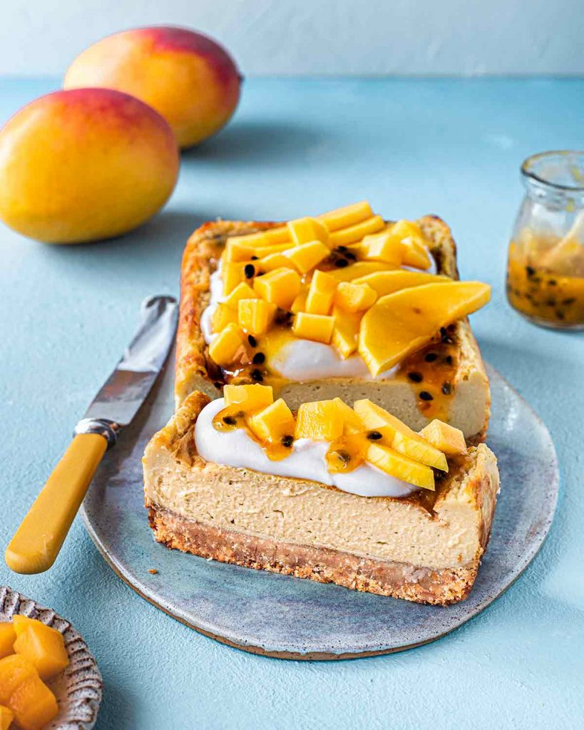 Baked vegan mango cheesecake on platter with one bar sliced off revealing its creamy texture