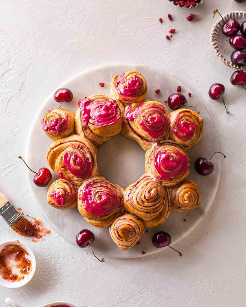 Cherry roll wreath on marble board. The wreath is partially iced with a bright pink glaze. Image shows final result of cherry wreath recipe.