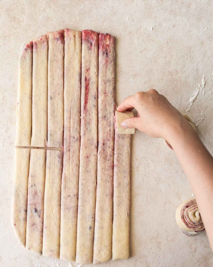 Dough for the cherry rolls is flattened and cut into strips. A hand is rolling one strip into a roll.