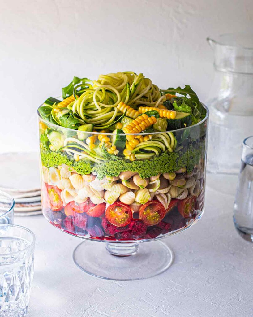 Vegan Layered Pasta Salad with Pesto in trifle glass with serving jugs and water surrounding