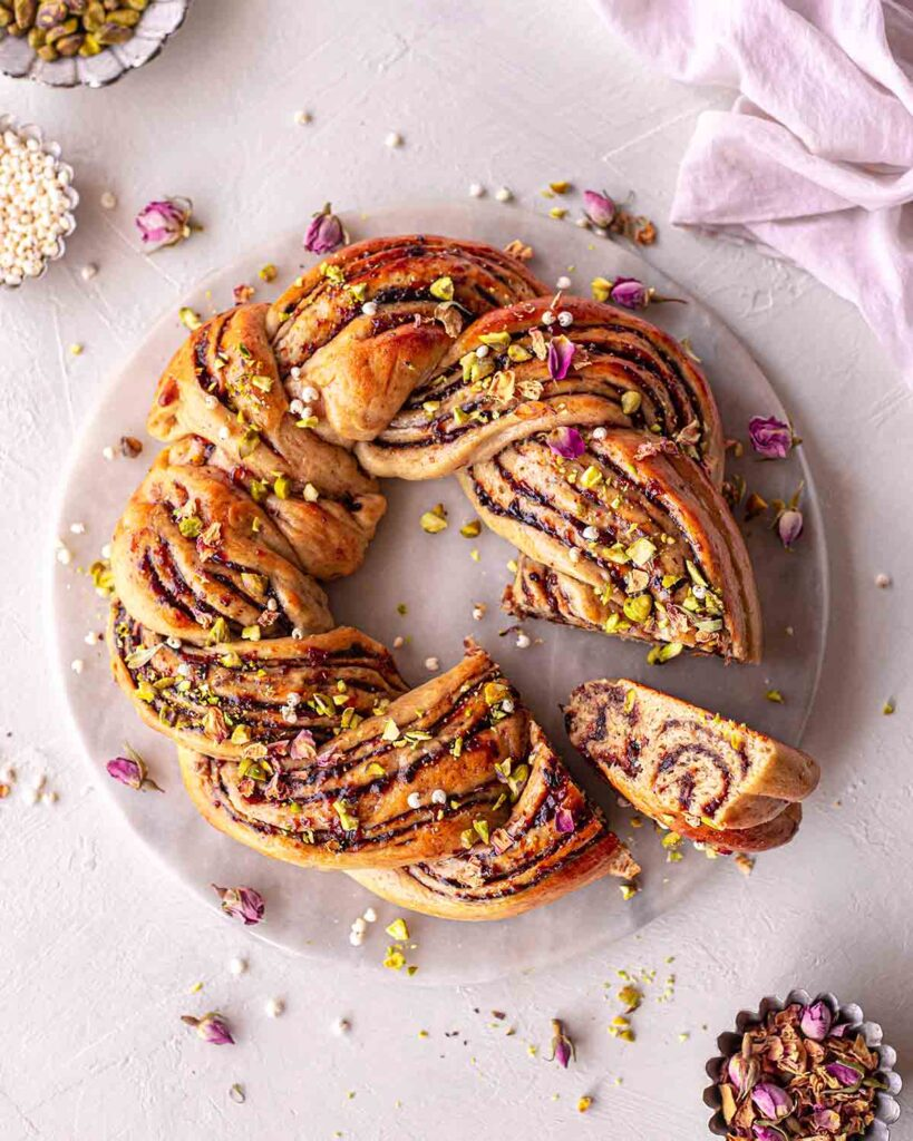 Christmas wreath bread on serving platter with a small slice coming out showing the beautiful swirls of Christmas fruit mince