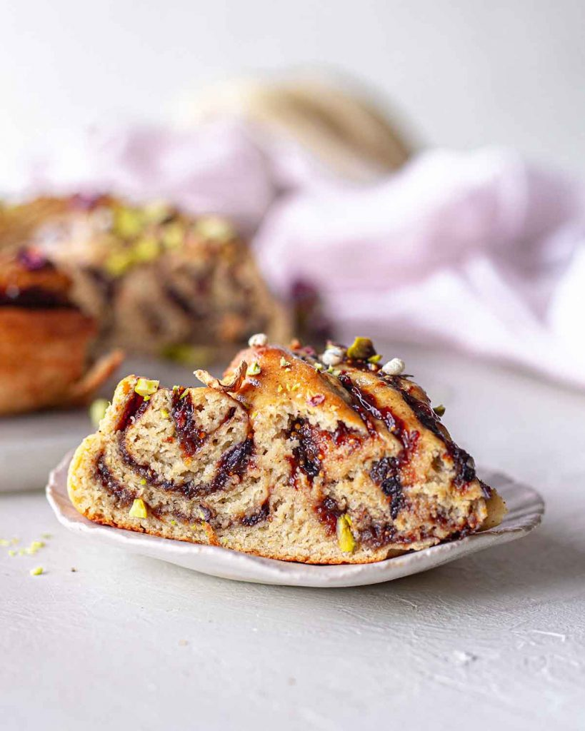 Close up of one slice of the Christmas bread wreath showing generous amount of fruit filling and a fluffy brioche-like golden bread.
