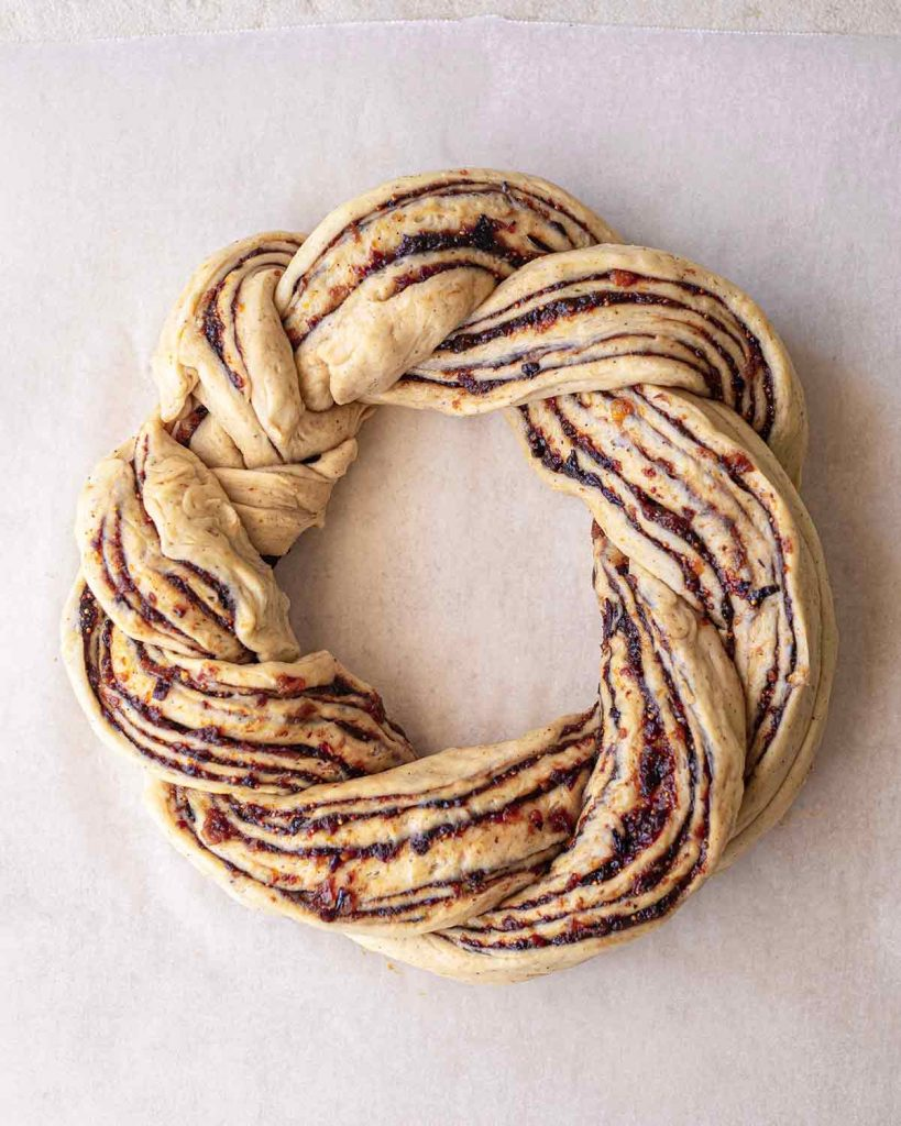 Unbaked Christmas bread wreath on a piece of baking paper