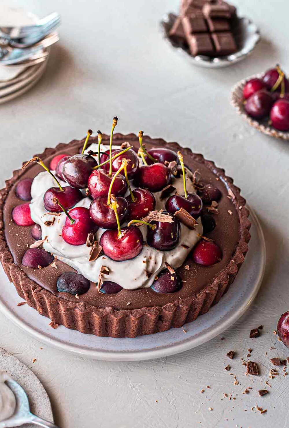 Vegan Blackforest tart with a chocolate base, ganache filling, coconut cream topping and lots of cherries on top. Tart is on plate surrounded by more fresh cherries and serving plates