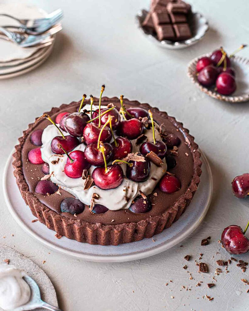 Vegan Black Forest tart with a chocolate base, ganache filling, coconut cream topping and lots of cherries on top. Tart is on plate surrounded by more fresh cherries and serving plates