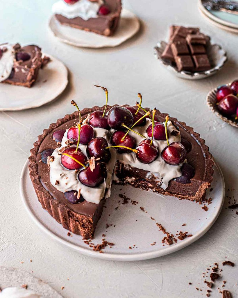 Vegan black forest tart on plate with two slices removed. Angle of picture shows creamy texture of the ganache filling