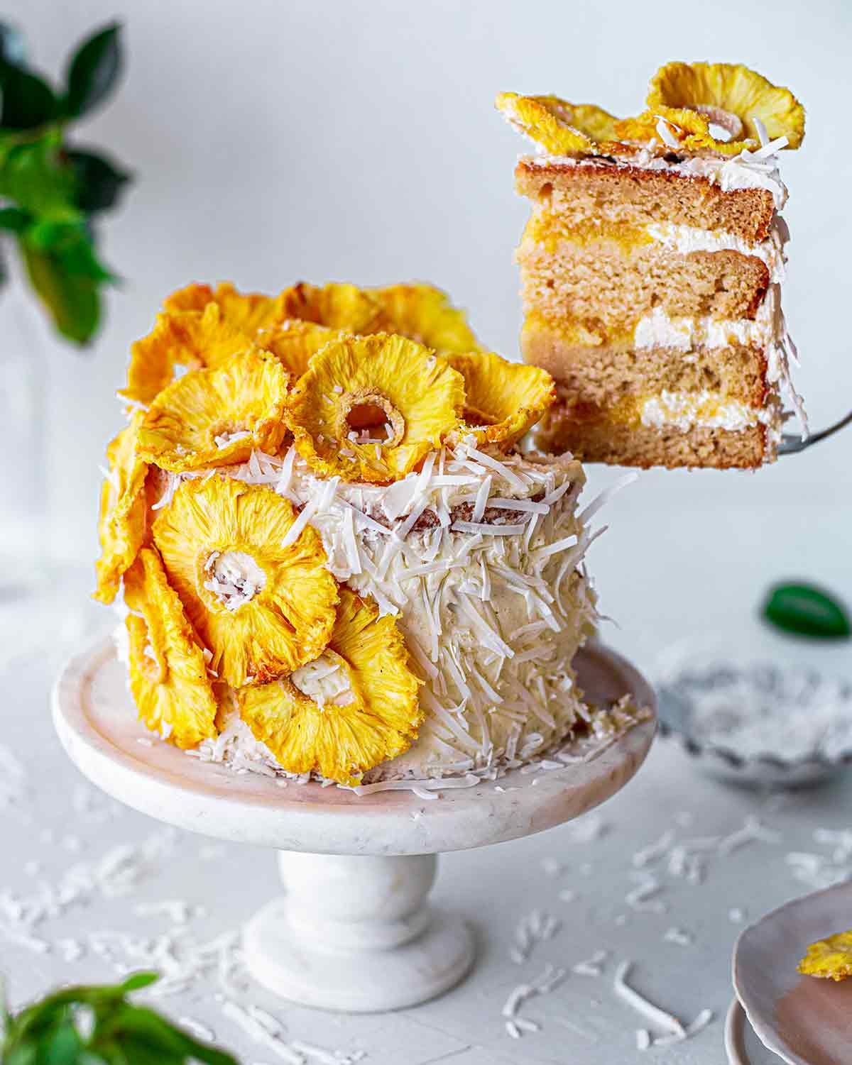 Vegan pina colada cake with slice lifted out with a cake server