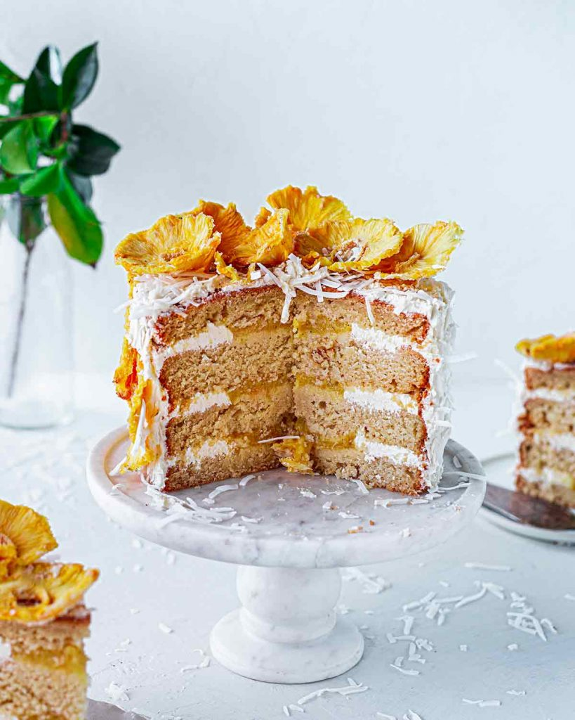 Cross section of whole vegan pina colada cake showing multiple layers of cake, pineapple puree, frosting and dried pineapple on top.