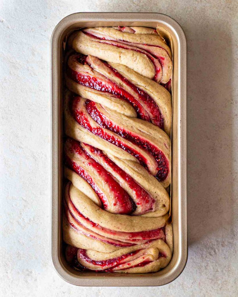 Unbaked raspberry jam donut babka in long loaf tin