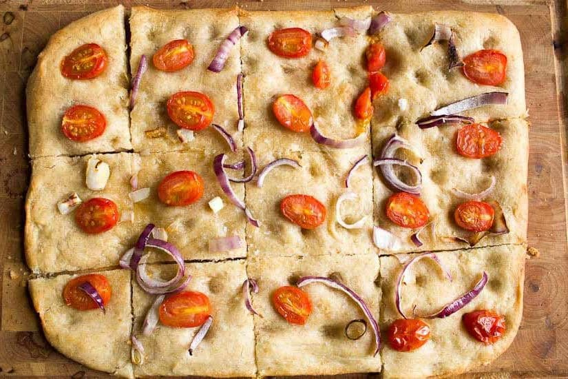 Sourdough focaccia with chopped cherry tomatoes and red onion slices cut into segments on chopping board