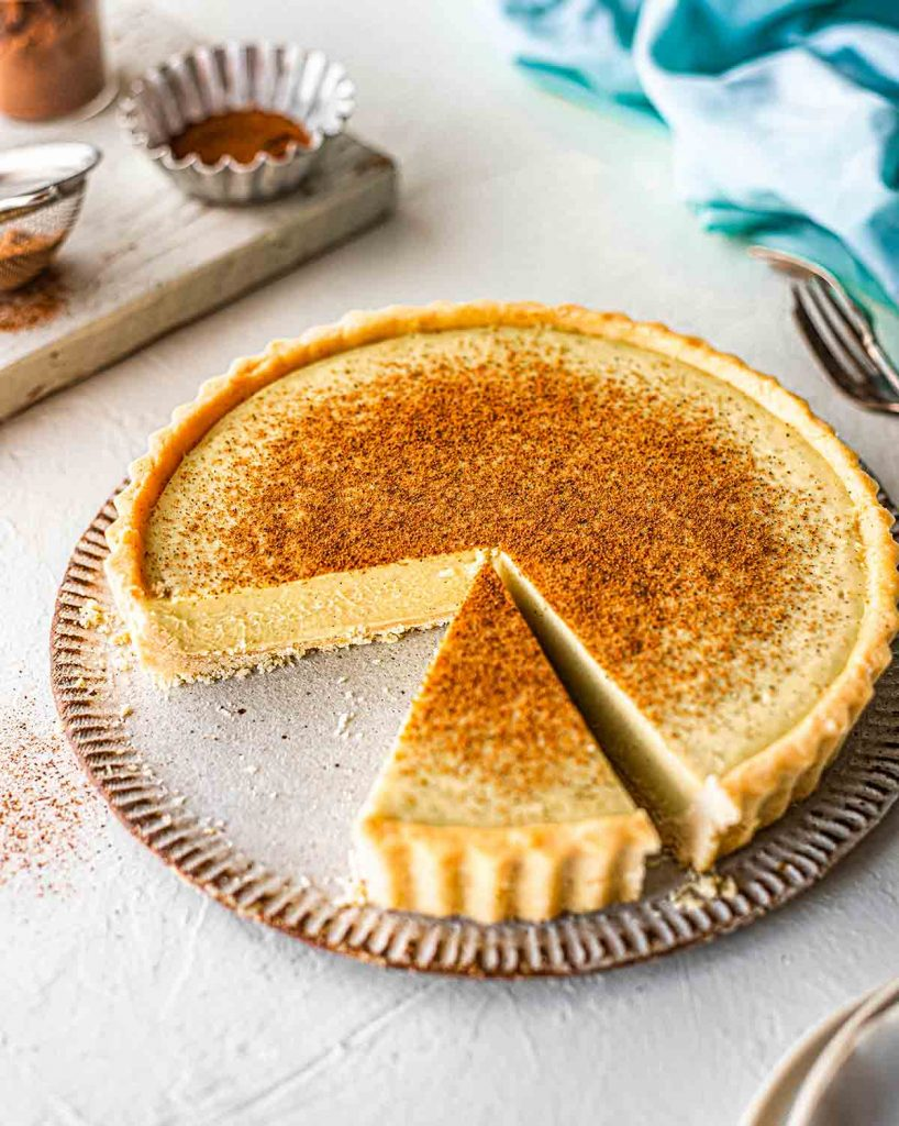 45 degree angle photo of vegan custard tart. Two slices taken out showing creamy and thick texture of custard pie.
