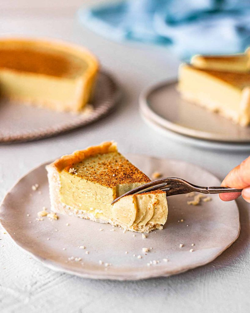 Close up of fork taking a bite out of one slice of the custard tart