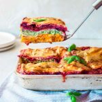 Vegan Rainbow Lasagna in casserole dish with slice lifted out revealing all the colourful layers
