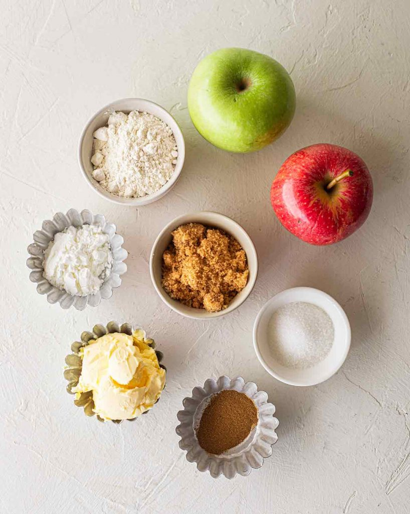 Flatlay of ingredients for vegan apple pie including: apples, flour, corn starch, brown sugar, regular sugar, vegan butter and spices