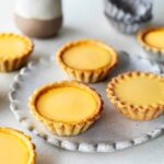 Multiple vegan egg tarts on a scalloped plate and around. Focus is on one tart.