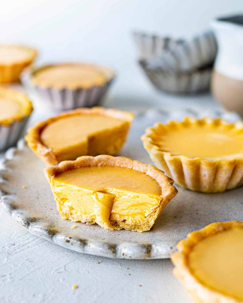 Close up of cut vegan egg tart showing silky custard interior and thin crumbly pastry