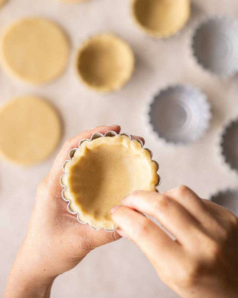 Close up of two hands pressing a round of pastry in a greased mini tart tin
