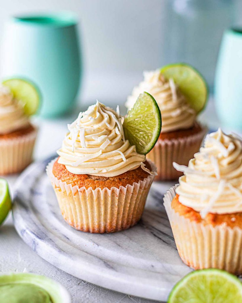 Vegan coconut lime cupcakes on marble board. Each cupcake has piped frosting, a wedge of lime and shredded coconut on top