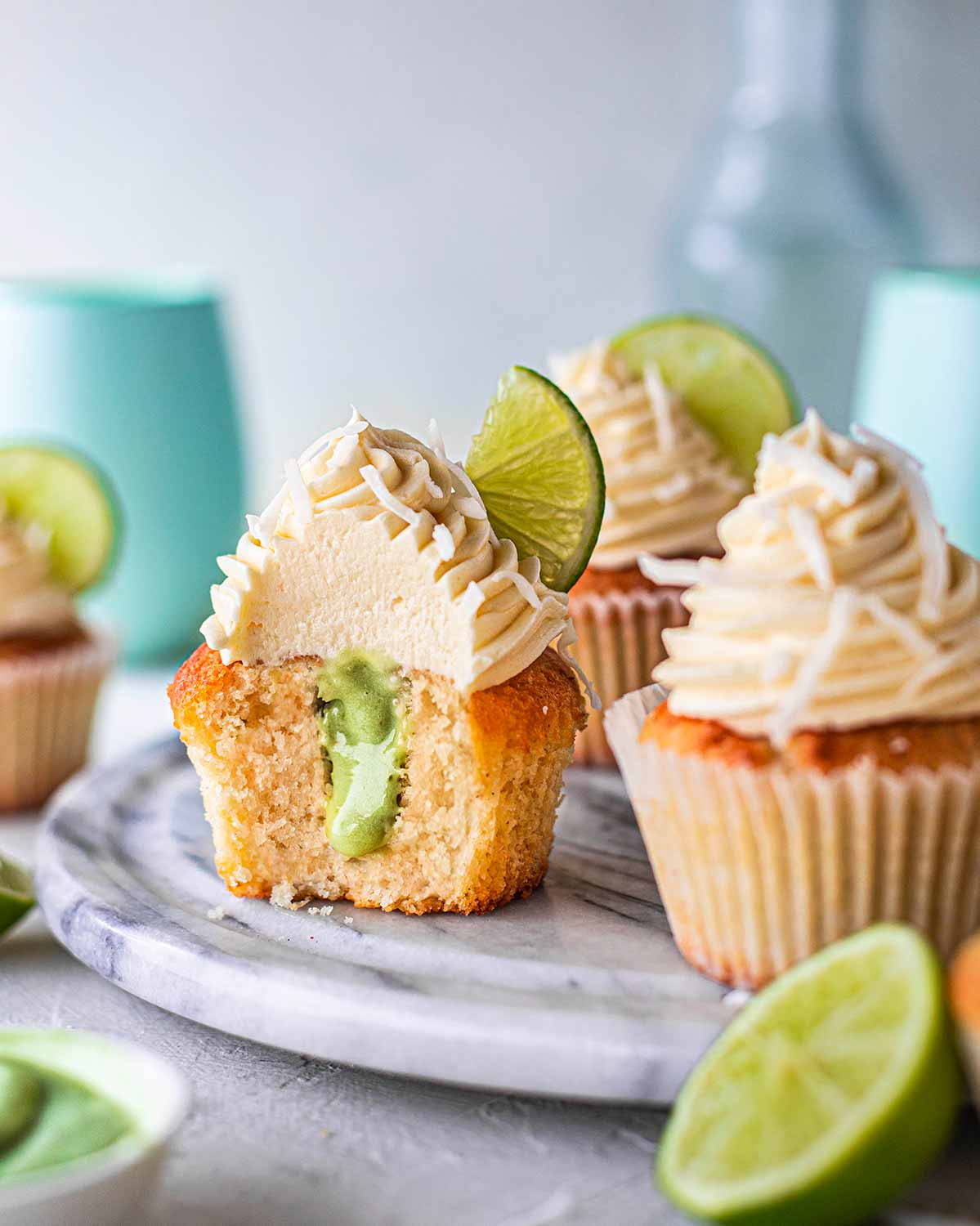 Vegan coconut lime cupcakes on marble board. One cupcake has a bite taken out of it showing the pastel green lime curd filling