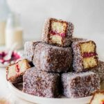 Stack of vegan lamingtons on a plate showing fluffy vanilla sponge and jam
