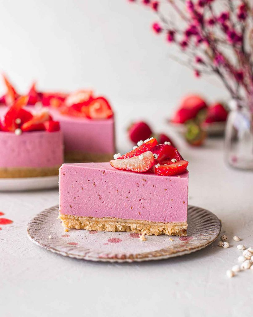 Close up of vegan strawberry cheesecake made with agar powder instead of coconut oil. The cake has very straight edges showing that it's firmer than the cheesecake made with coconut oil.