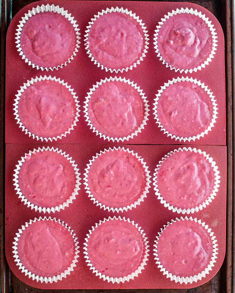 Overhead image of pink cake batter in 12 cupcake moulds.
