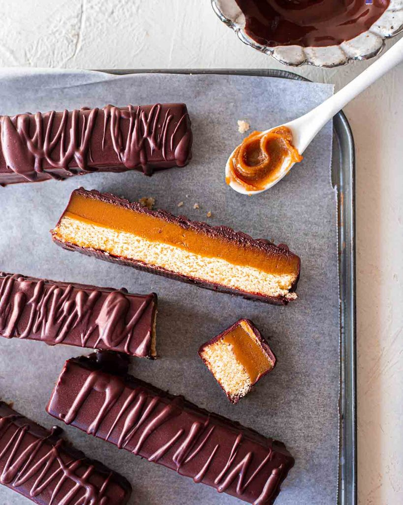 Flatlay of vegan twix bars on lined baking tray. One twix bar is sliced lengthways showing smooth caramel and golden cookie base.