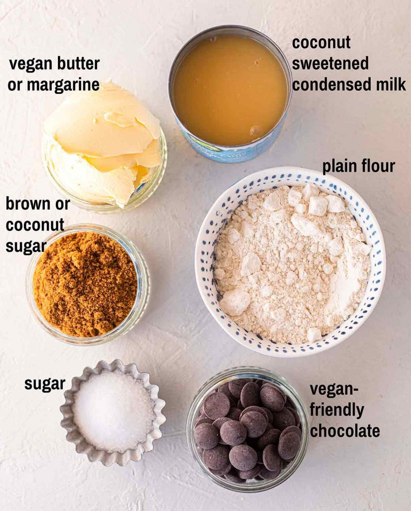 Flatlay of ingredients for twix bars including sweetened condensed milk, vegan butter/margarine, plain flour, brown or coconut sugar, cane sugar and vegan-friendly chocolate