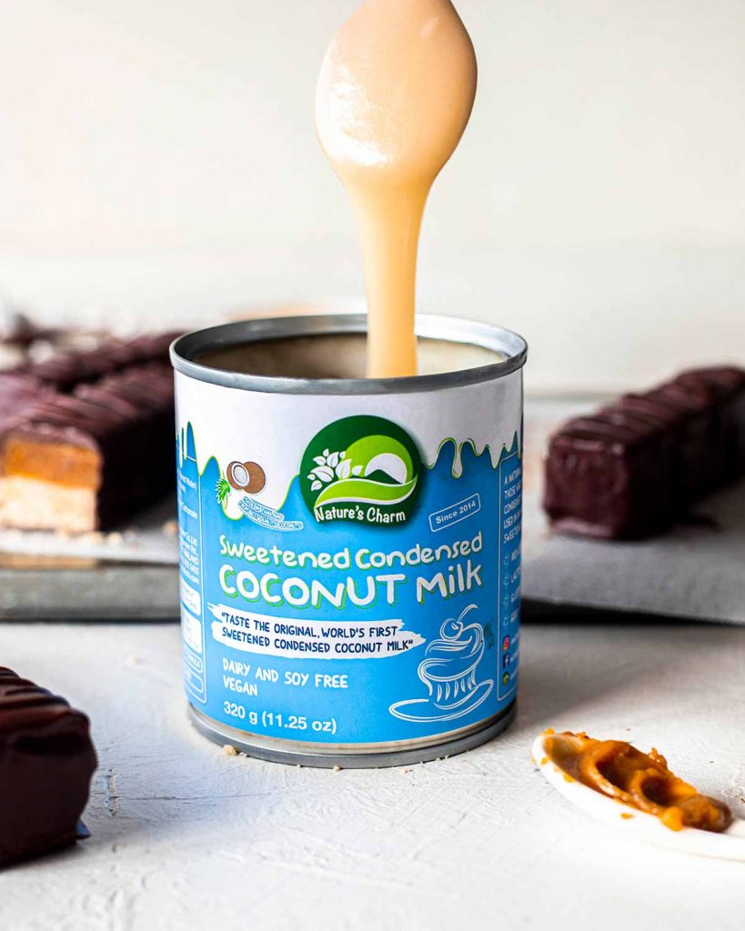 Close up of Nature's Cham Sweetened Condensed Coconut milk with a spoon coming out showing the thick texture