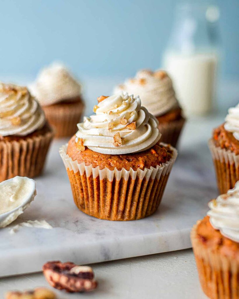 The best vegan carrot cake cupakes with piped cream cheese frosting on a marble serving board