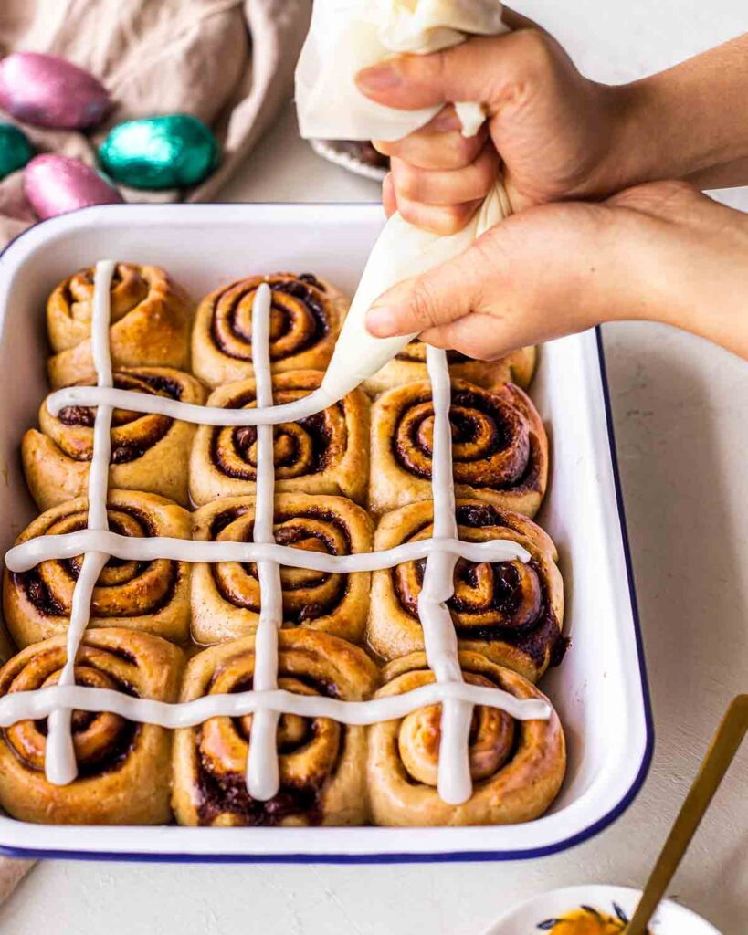 Vegan cinnamon rolls in a baking tray with two hands piping cream cheese frosting cross on the rolls