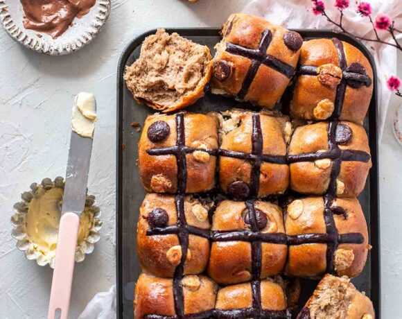 Double chocolate chip hot cross buns on baking tray. Two hot cross bun are cut open and has butter spread on one side. The other side is exposed showing soft bread and melting chocolate chips.